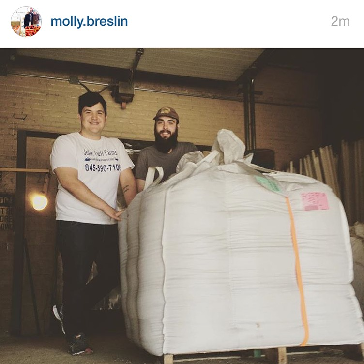 Alex and Wes receiving a whole lot of wheat from Breslin Farm.